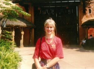 blonde haired lady standing in the sun smiling into the camera